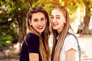 summer. two girls smile. park and wa