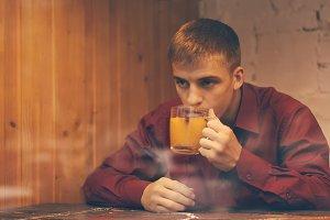 Guy drinks tea in cafe in fall