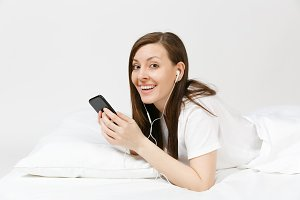 Calm young woman lying in bed with w