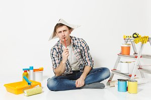 Pensive man in newspaper hat with pe