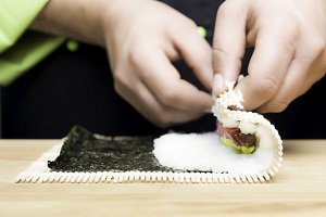hands rolling up sushi