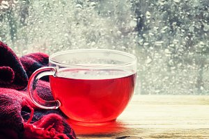 Cup with hot red tea in front of a w
