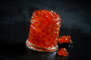 Red caviar in a glass jar on black s
