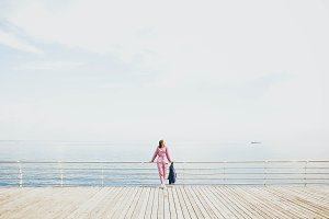 Girl relaxing on pier at the sea