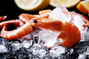 Frozen shrimps on crushed ice on a d
