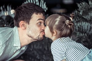 Dad kisses little daughter