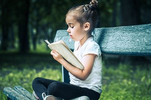 little girl is sitting on a bench an