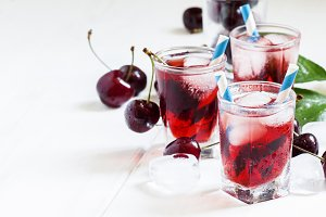 Cold cherry juice with ice on a whit
