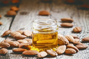 Almond oil in a small jar of almonds