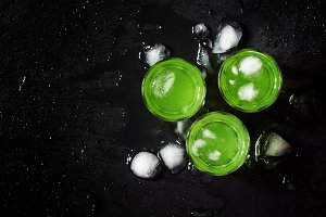 Green mint drink with ice on a dark