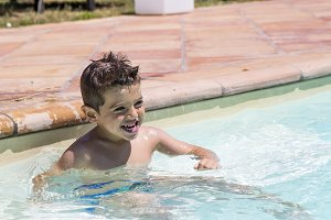 Cute little boy playing in the pool