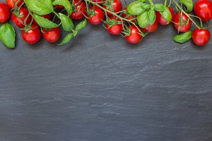 Cherry tomatoes with basil leaves on