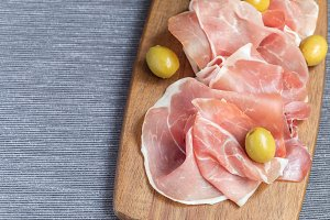 Prosciutto ham with green olives on
