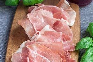 Prosciutto ham on wooden board, basi