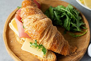 Tasty croissant sandwich with ham