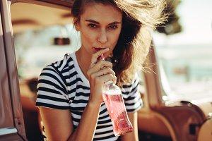 Woman drinking beverage on road trip