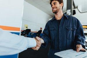 Auto mechanic shaking hands