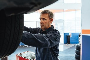 Mechanic changing wheel of a car