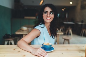 Young smiling woman in coffee shop