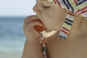 child eating fruit on the beach