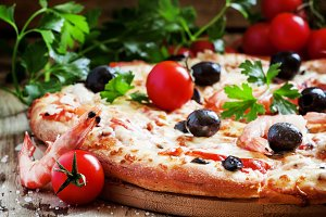 Pizza with seafood and black olives,