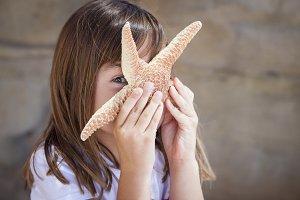 Young Girl Playing with Starfish
