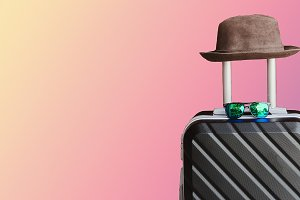 a suitcase with a hat and sunglasses