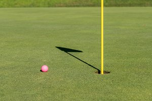 Pink golf ball by flag and hole on