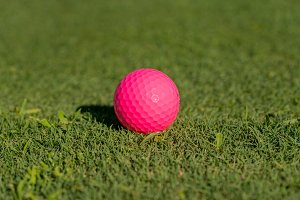 Pink golf ball on the edge of
