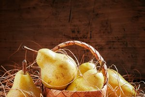 Ripe yellow pears in a wicker basket