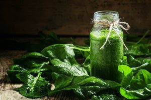 Spinach smoothie in a glass bottle,