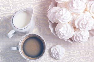 meringue cookies and a cup of coffee with cream