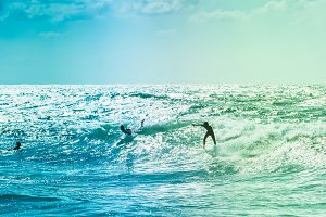 Surfers riding some waves on the sea