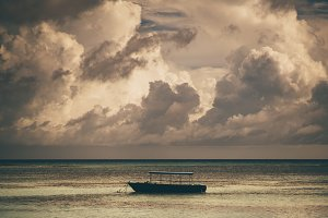 A covered anchored motorboat, sunset