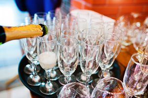 Pour champagne into glasses at weddi