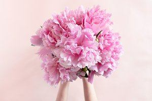 Hands hold bouquet of peonies