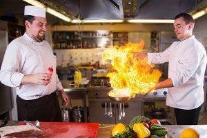 Chefs doing flambe on food