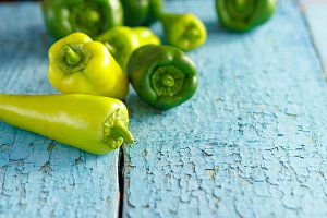 Green peppers, wooden background