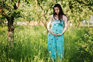 Pregnant woman on turqoise dress at