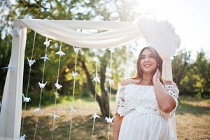Happy pregnant woman on white dress
