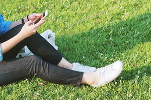 Woman using smartphone on grassland