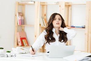 Businesswoman suffering neck pain