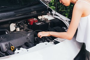 Asian woman checking her broken car