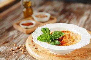 Fresh classic hummus with basil in t