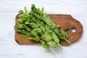 Green fresh mint on wooden board