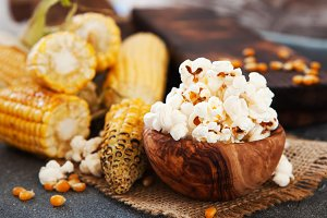 Popcorn in a olive wooden bowl on a