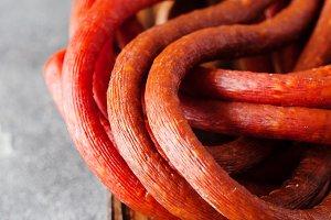 Long thin dry sausage on dark slate
