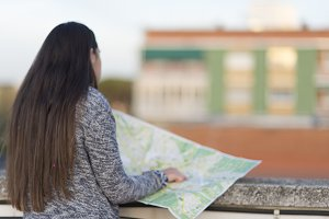 young woman with map against panoram