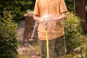 kid hands hold hose with squirting