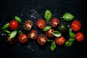 Red and black halves of tomatoes wit